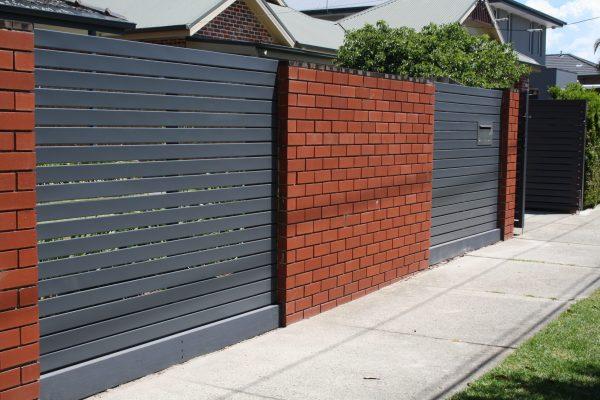 Blue Smartslat Fencing with concealed posts between brick walls