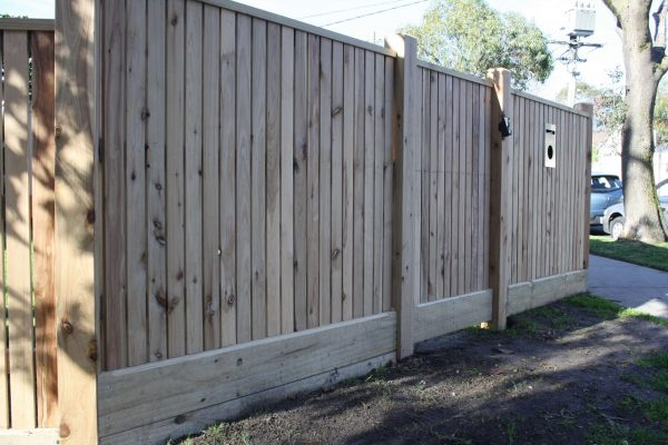 Feature picket fence with gabled Lipped Capping and sleeper to retain soil behind fence